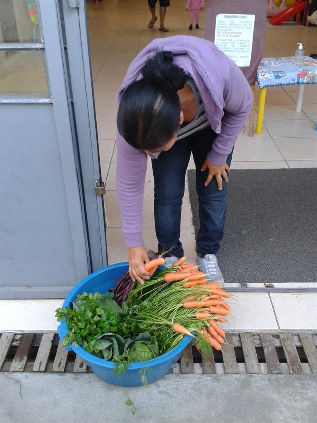 Pais levando pra casa as hortaliças colhidas da horta do CMEI.