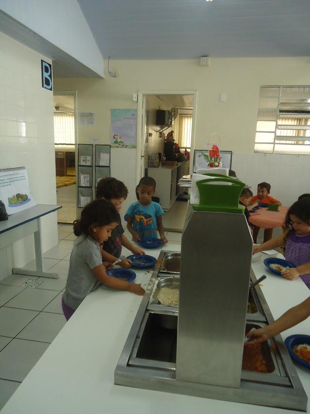 crianças servindo-se no almoço