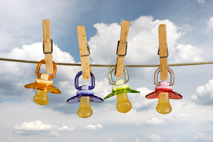 Colored baby pacifiers hanging outside in line