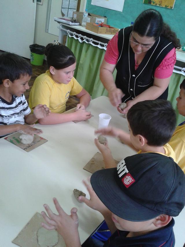 Utilizando argila, estudantes constroem um vulcão.