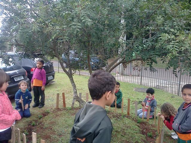 Crianças fazendo o jardim.