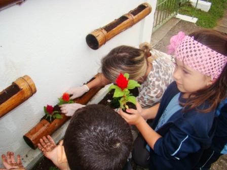 Alunos do Pré ajudando a plantar flores na horta s