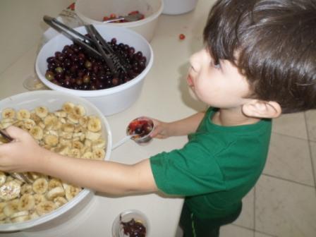 Crianças degustando frutas com chocolate