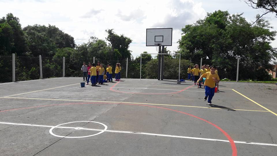 Estudantes brincam, cooperando uma com outro.