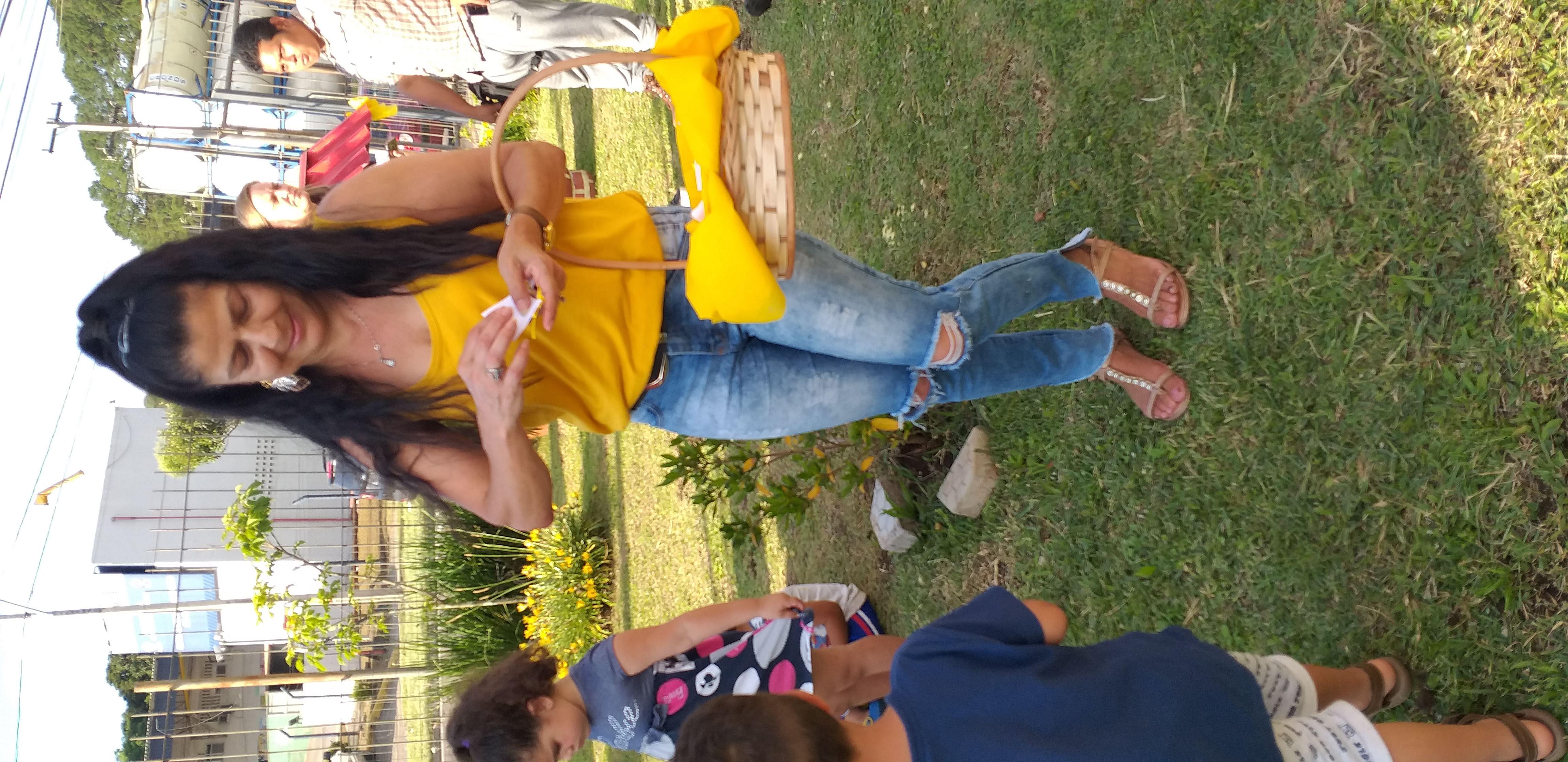 professora Zenaide oferecendo as lembrancinhas de mel para as crianças e família
