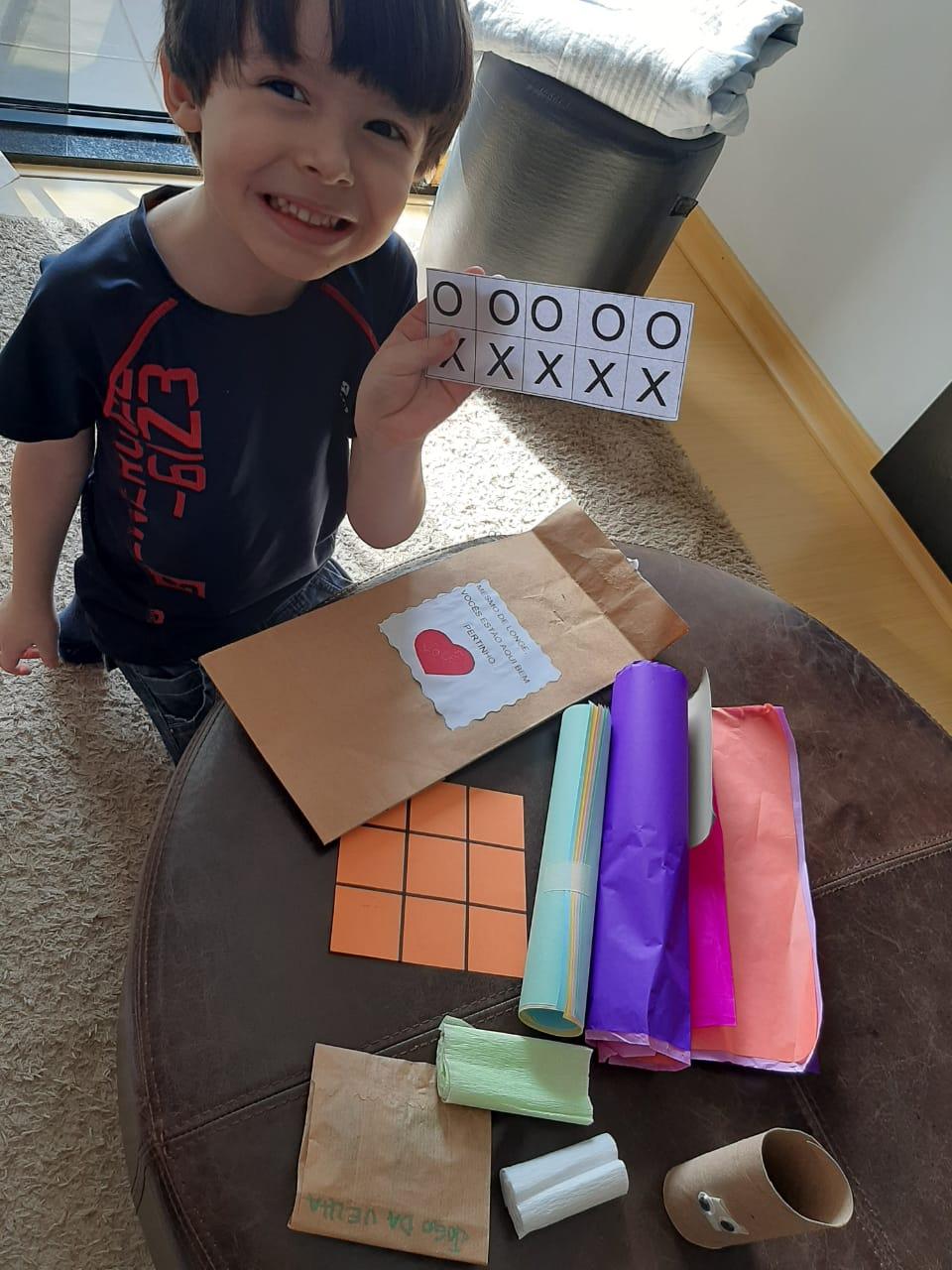 Felipe brincando em casa com o material recebido no kit pedagógico