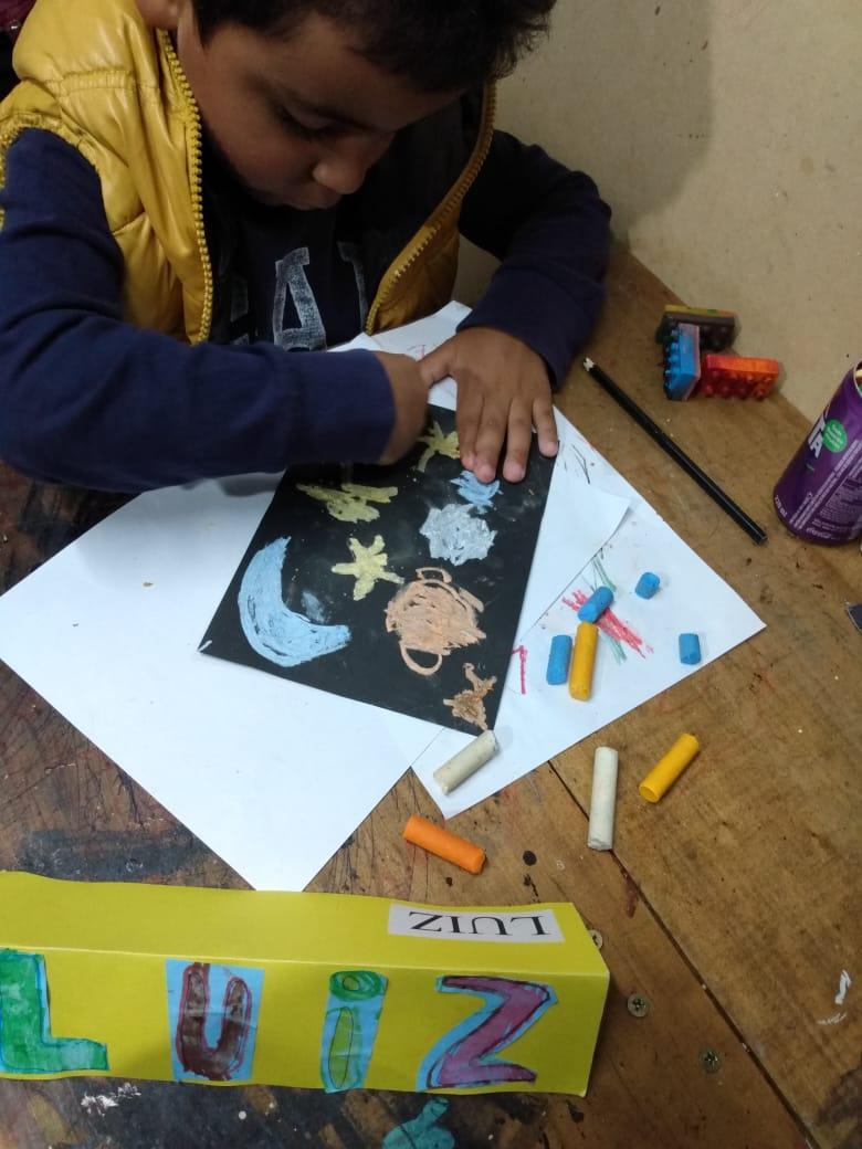 Luiz (turma Pré II) fazendo atividade com o material recebido no kit