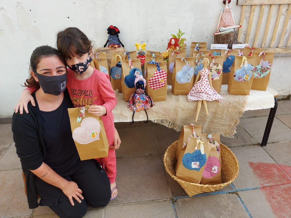 Mãe e crianças recebendo o kit montado pelas professoras